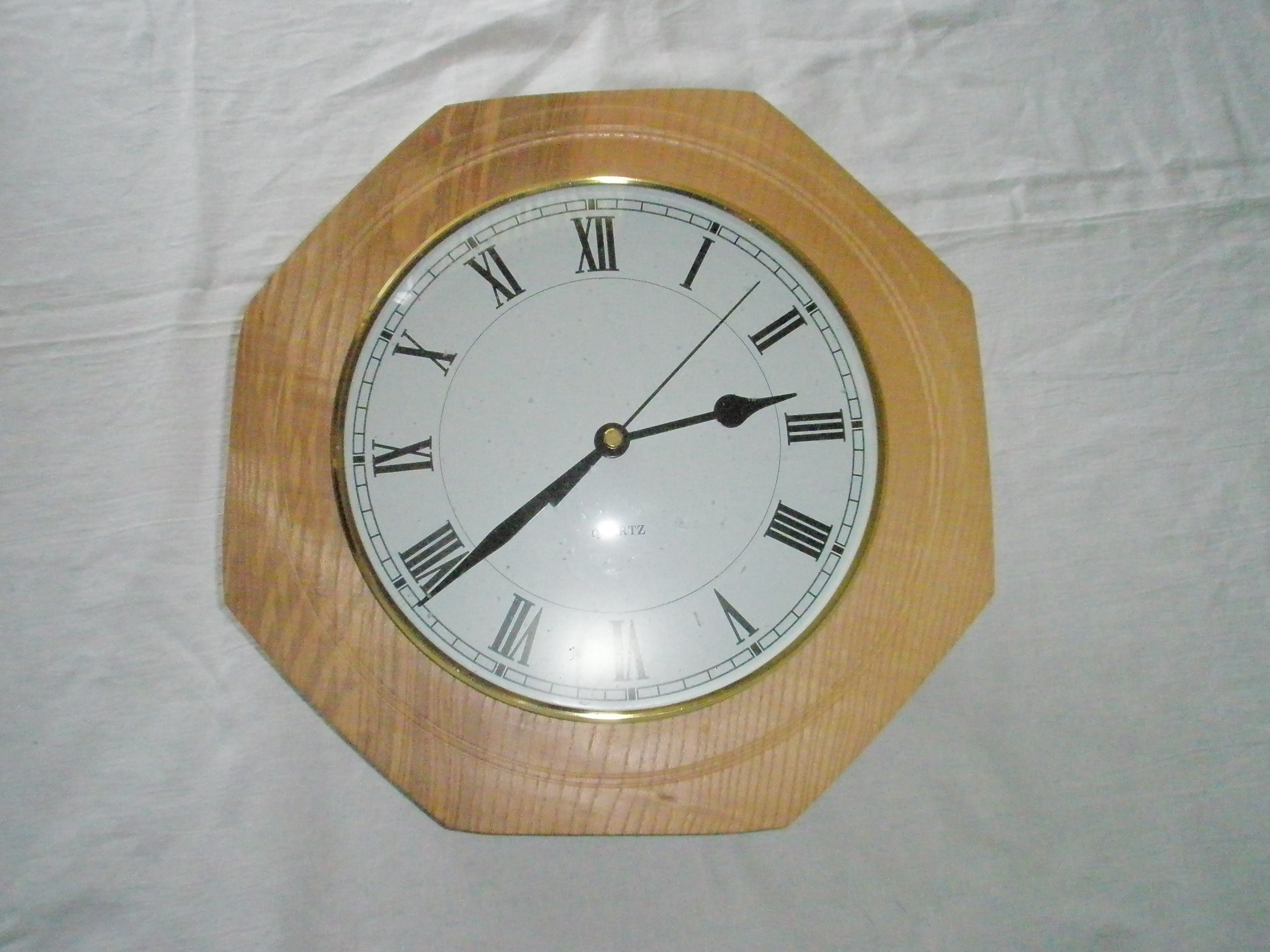 wall mounted round white face clock with black numerals in an eight sided Ash surround